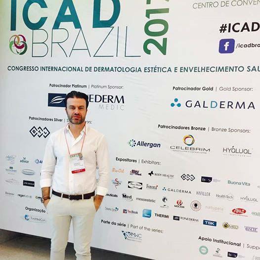 A imagem mostra o Dr. Felipe Meletti em frente a um banner de um evento.